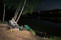 Рыбак ловит рыбу ночью