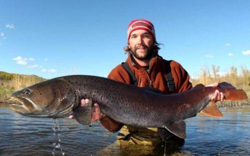 Рыбак держит тайменя