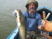 Рыбак держит сома